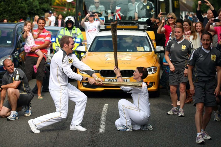 JULY 08: An unusual hand-over as Torchbearer Riessen Hill passes the Olympic Flame to Torchbearer Sarah Toll on the Torch Relay leg between Hatfield and St. Albans in St. Albans, England. (LOCOG via Getty Images)