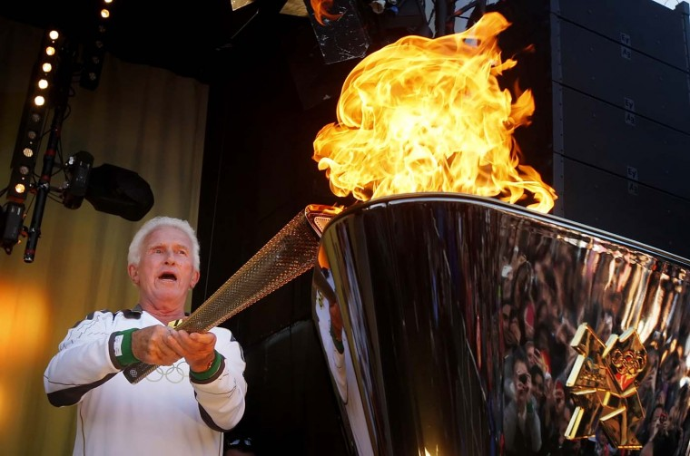 JULY 08: Torchbearer David Cole lights the cauldron with the the Olympic Flame during the Torch Relay leg through Luton on July 8, 2012 in St Albans, England. (LOCOG via Getty Images)