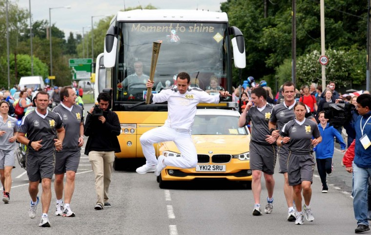 JULY 09: Mexican international footballer and Torchbearer Gerardo Torrado carries the Olympic Flame on the Torch Relay leg between Aylesbury and Stoke Mandeville. (LOCOG via Getty Images)