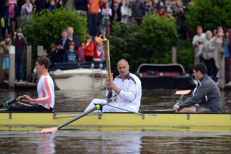 JULY 10: Former Olympic gold medalist rower and Torchbearer Sir Steve Redgrave carries the Olympic Flame on a boat on the River Thames on the Torch Relay leg between Wallingford and Henley on Thames during Day 53 of the London 2012 Olympic Torch Relay. (LOCOG via Getty Images)