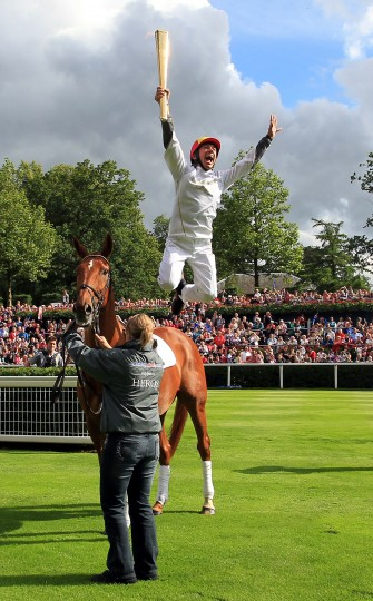 JULY 10: Jockey Frankie Dettori leaps from ex-racehorse Monsignor, after they carried the Olympic Flame around the parade ring at Ascot Racecourse during Day 53 of the London 2012 Olympic Torch Relay in Windsor, England. (LOCOG via Getty Images)