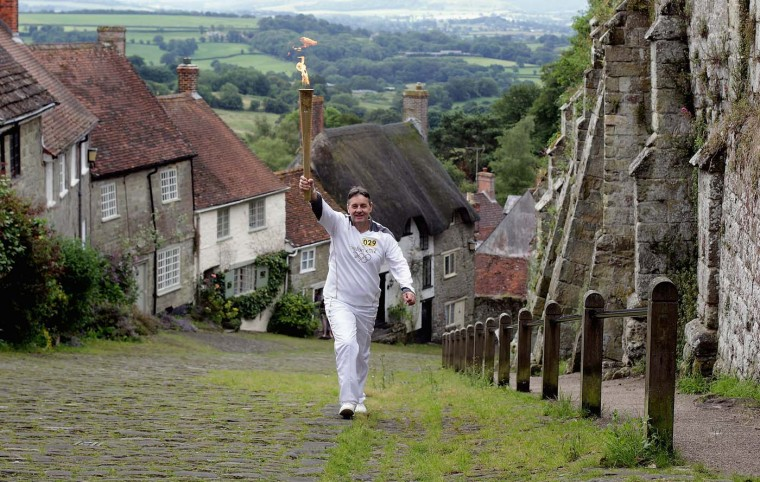 JULY 12: Torchbearer Alan Surtees, carries the Olympic Flame up Gold Hill as the Torch Relay on Day 55 of the London 2012 Olympic Torch Relay in Shaftesbury, England. (Matt Cardy/Getty Images)