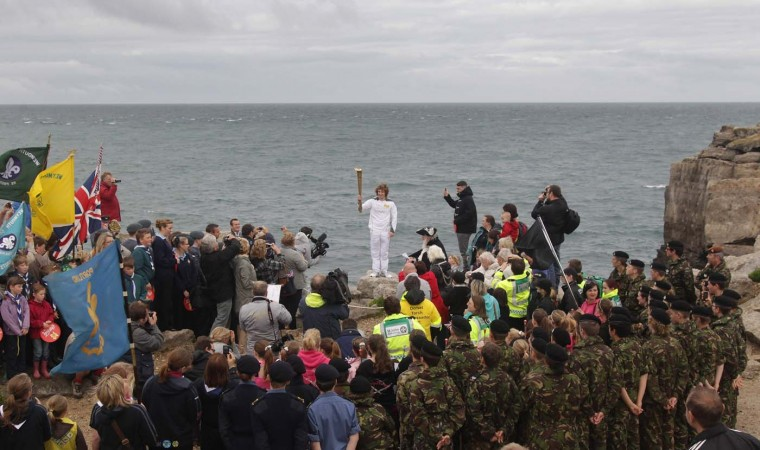 JULY 13: Torchbearer Thomas Mules holds the Olympic Flame on Pulpit Rock, Portland Bill, at the beginning of Day 56 of the London 2012 Olympic Torch Relay near Salisbury, England. (Matt Cardy/Getty Images)