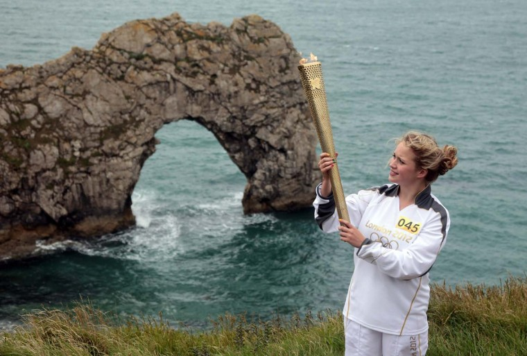 JULY 13: Torchbearer Lisa Devine holds the Olympic Flame in front of Durdle Door, during Day 56 of the London 2012 Olympic Torch Relay in Dorset, England. (Matt Cardy/Getty Images)