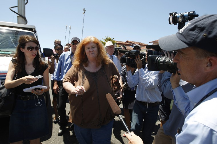 An unidentified family friend walks between members of the media as she leaves the home of Robert and Arlene Holmes, parents of 24-year-old mass shooting suspect James Holmes, on July 20, 2012 in the Rancho Penasquitos area of San Diego, California. James Holmes reportedly killed 12 people and wounded scores of others at a midnight opening of the Barman movie, The Dark Knight Rises. (David McNew/Getty Images)