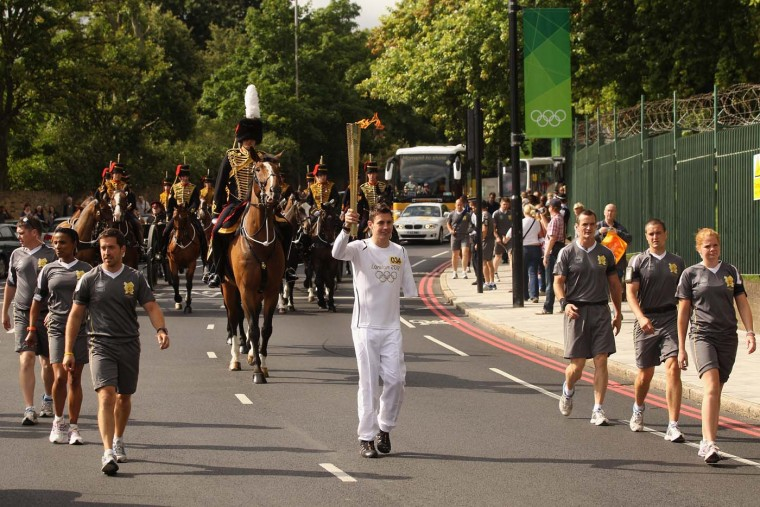 LONDON, ENGLAND - JULY 21: Torchbearer Jaco van Gass (C), a soldier with the First Battalion, The Parachute Regiment, who was severely wounded in Afghanistan, is followed by the Kings Troop Royal Horse Artillery as he carries the Olympic torch past Woolwich Barracks on July 21, 2012 in London, England. (Oli Scarff/Getty Images)
