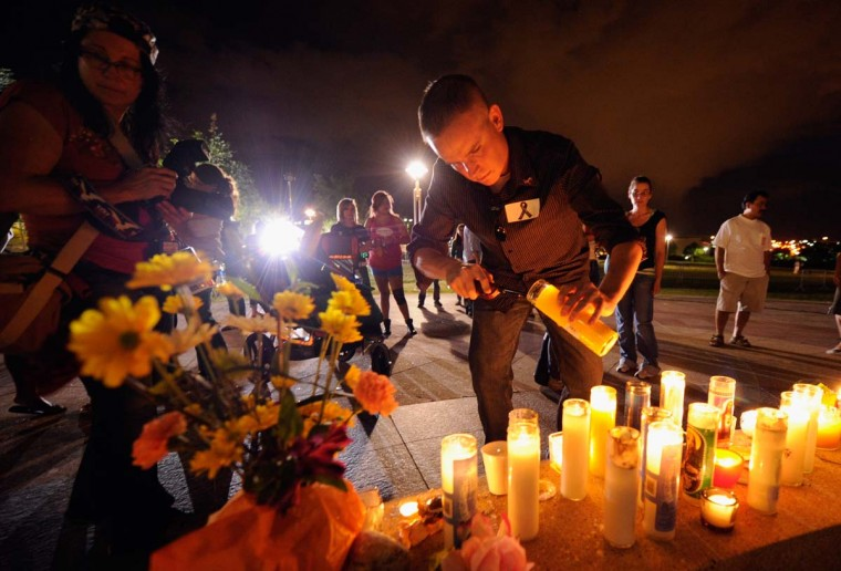 A man lights a candle as mourners gather at the fountain of Aurora Municipal Center after a prayer vigil for the 12 victims of Friday's mass shooting at the Century 16 movie theater in Aurora, Colorado. (Kevork Djansezian/Getty Images)