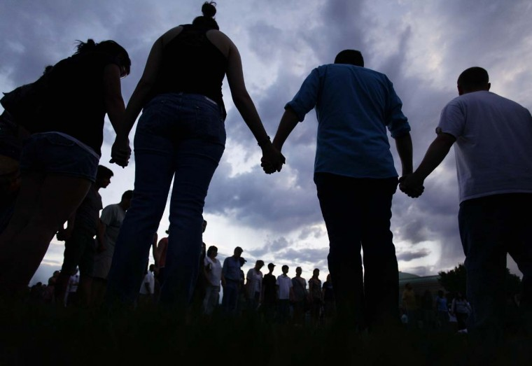 People hold hands as they pray during a memorial service outside the Aurora Municipal Center in Aurora, Colorado. The memorial was for the victims that were killed and wounded during the mass shooting at a movie theater last Friday. (Joshua Lott/Getty Images)