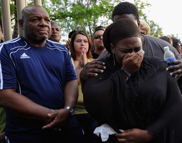 A woman is comforted when she is overcome with grief during a prayer vigil for the victims of Friday's movie theater mass shooting at the Aurora Municipal Center in Aurora, Colorado. (Kevork Djansezian/Getty Images)