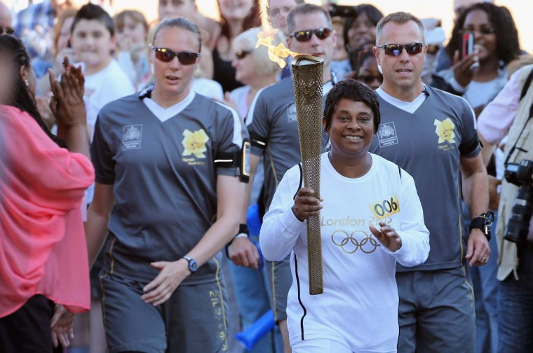 Doreen Lawrence, mother of murdered teenager Stephen Lawrence, carries the Olympic Torch into the Stephen Lawrence Charitable Trust Centre for the hand over to Kieran Lang, The Young Mayor of Lewisham on July 23, 2012 in London, England. (Dan Kitwood/Getty Images)