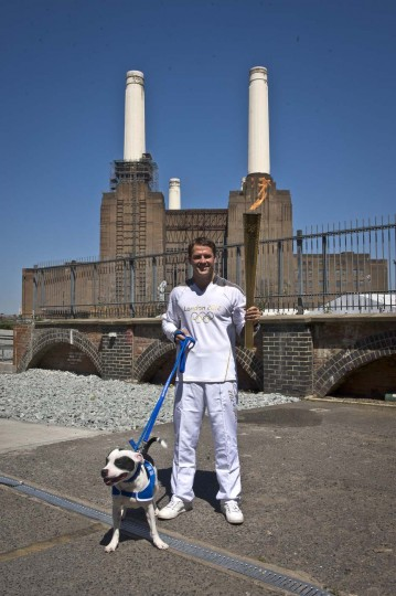 LONDON, UNITED KINGDOM - JULY 23: Torchbearer Michael Owen carries the Olympic Flame at Battersea Dogs and Cats Home during Day 66 of the London 2012 Olympic Torch Relay on July 23, 2012 in London, England. (LOCOG/Getty Images)