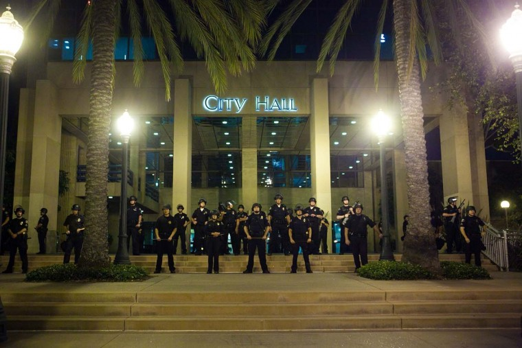 A line of police officers protect Anaheim City Hall during demonstrations to show outrage for the fatal shooting of Manuel Angel Diaz, 25, at Anaheim City Hall on July 24, 2012 in California. (Jonathan Gibby/Getty Images)