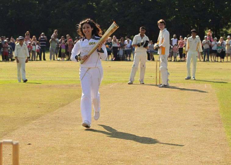 HARROW, UNITED KINGDOM - JULY 25: Torchbearer 001 Joanna Hyams carries the Olympic Flame on the wicket at Pinner Cricket Club in Harrow at the beginning of Day 68 of the London 2012 Olympic Torch Relay on July 25, 2012 in London, England. (LOCOG/Getty Images)