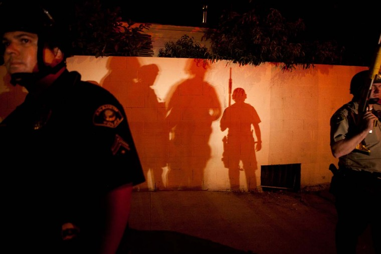 Police officers stand guard after protesters set fire to a near by trash bin during a demonstration to show outrage for the fatal shooting of Manuel Angel Diaz, 25, at Anaheim City Hall on July 24, 2012 in California. (Jonathan Gibby/Getty Images)