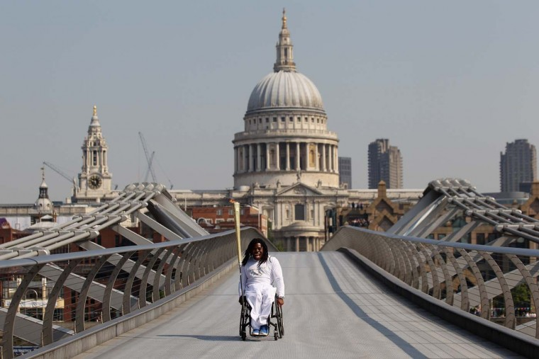 LONDON, ENGLAND - JULY 26: Wheelchair basketball player Adedoyin Adepitan carries the Olympic flame over Millennium Bridge in front of St Paul's Cathedral during Day 69 of the London 2012 Olympic Torch Relay on July 26, 2012 in London, England. (Oli Scarff/Getty Images)