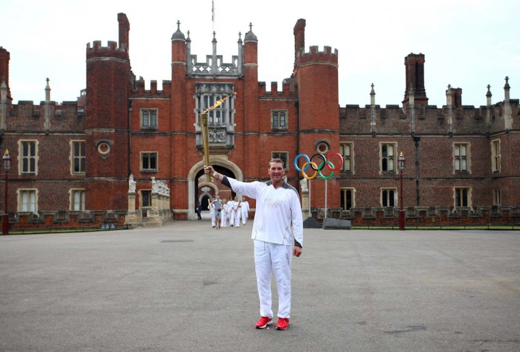 LONDON, UNITED KINGDOM - JULY 27: Olympic Gold Medalist rower Torchbearer 011 Matthew Pinsent stands in front of the Great Gate at Hampton Court Palace holding the Olympic Flame during the final Day of the London 2012 Olympic Torch Relay on July 27, 2012 in London, England. (LOCOG/Getty Images)