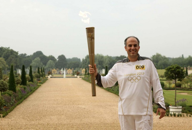 LONDON, UNITED KINGDOM - JULY 27: Torchbearer 009 Mark Levy holds the Flame in the grounds of Hampton Court Palace during the final day on July 27, 2012 in London, England. (LOCOG/Getty Images)