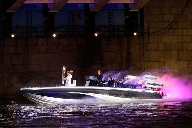 David Beckham passes under Tower Bridge driving a speedboat named 'Max Power' which carries the Olympic Torch with its torchbearer on July 27, 2012 in London, England. Athletes, heads of state and dignitaries from around the world have gathered in the Olympic Stadium for the opening ceremony of the 30th Olympiad. London plays host to the 2012 Olympic Games which will see 26 sports contested by 10,500 athletes over 17 days of competition. (Matthew Lloyd/Getty Images)