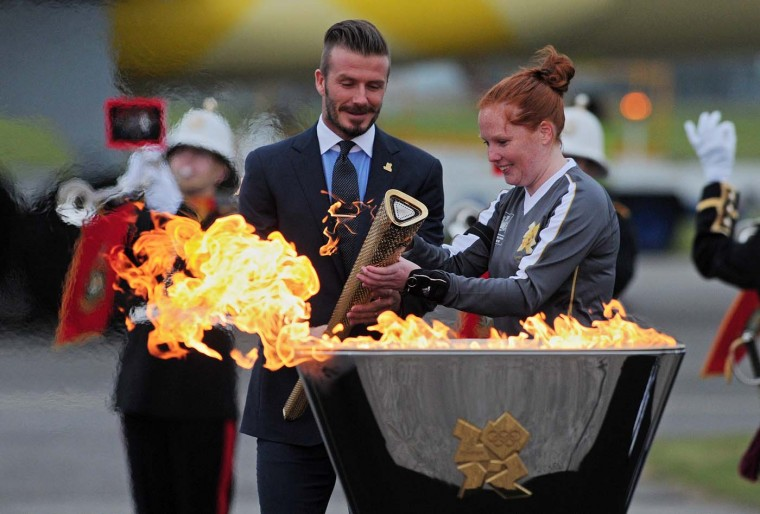 MAY 18: Former England footballer David Beckham (L) lights the Olympic Torch as it arrives at RNAS Culdrose air base in Cornwall, south-west England, on May 18, 2012. The Olympic Torch relay will kickoff from Land's End, the southwest tip of England. (Carl Court/AFP/Getty Images)