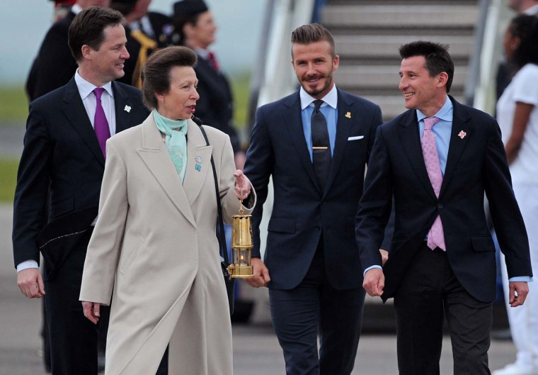 Britain's Princess Anne, Deputy Prime Minister Nick Clegg (L), 2012 Chairman Lord Sebastain Coe (R) and former England footballer David Beckham (2nd R) arrive with the Olympic flame at RNAS Culdrose air base in Cornwall, south-west England, on May 18, 2012. (Carl Court/AFP/Getty Images)