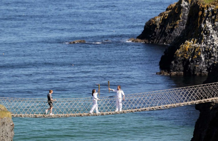JUNE 4: Olympic Torchbearers Clare Leahy (L) and Denis Broderick carry the torch over the Carrick-A-Rede rope bridge in Ballintoy, Northern Ireland, on June 4, 2012. (Peter Muhly/AFP/Getty Images)