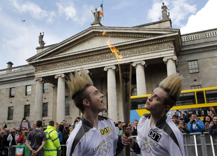 JUNE 6: Olympic Torchbearers and Irish pop stars John and Edward Grimes, known as Jedward, carry the torch during their relay leg to the General Post Office in Dublin, Ireland on June 6, 2012. (Peter Muhly/AFP/Getty Images)