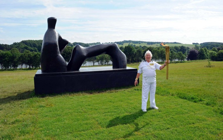 JUNE 25: Muriel Brown, 81, from Manchester, carries the Olympic Flame to the Henri Moore sculpture in the Yorkshire Sculpture Park near Wakefield as part of the 2012 London Olympic Torch Relay. Muriel was selected through the Coca-Cola campaign for her 60 years service to Amateur Athletics Coach and Judge Competitor Committees. (Paul Ellis/AFP/Getty Images)