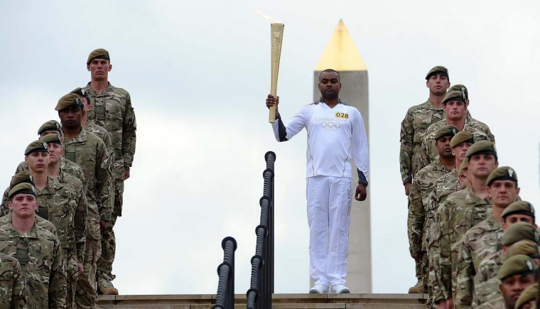 Decorated Lance Corporal Johnson Beharry carries the Olympic flame past the National Armed Services Memorial to mark Armed Forces Day during the Olympic Torch relay in Alrewasm central England on June 30,2012. (Paul Ellis/AFP/Getty Images)