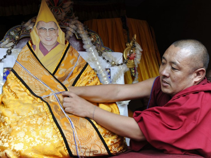 An exiled Tibetan Buddhist monk prepares a decorated portrait of Tibetan spiritual leader The Dalai Lama in honour of his 77th birthday at Boudha in the outskirts of Kathmandu. Thousands of Tibetans gathered to mark the Dalai Lama's 77th birthday on July 6, with the Nepalese government saying it would not tolerate anti-China activities on its soil. (Prakash Mathema/AFP/Getty Images)