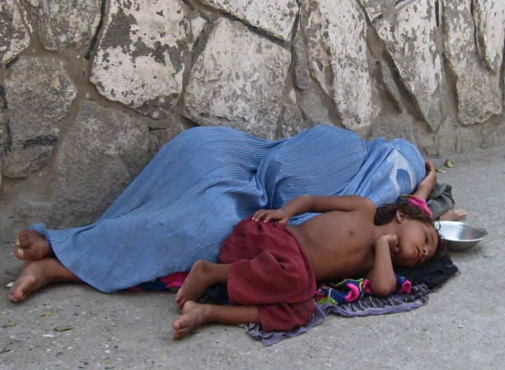 An Afghan woman and a child rest on the ground as they beg in the city of Jalalabad on July 8, 2012. The war-torn country still faces poverty, unemployment and lack of infrastructure.Noorullah Shirzada/AFP/Getty Images)