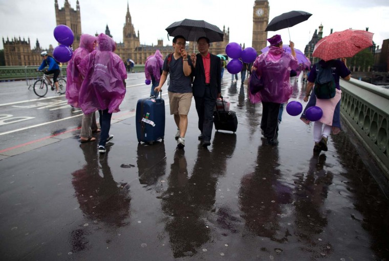 People walk along Westminster Bridge during a rain shower in central London on July 8, 2012. (Andrew Cowie/AFP/Getty Images)