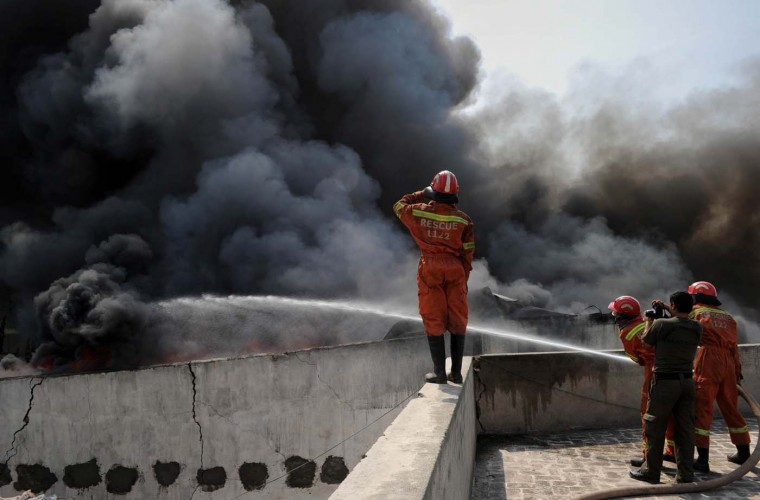 Pakistani firefighters use a hose as they attempt to extinguish a fire at a United Nations High Commission for Refugees (UNHCR) warehouse in Peshawar on July 8, 2012. Relief supplies including thousands of tents have been destroyed in the fire at the warehouse in the Chamkini area of the city. (A. Majeed/AFP/Getty Images)
