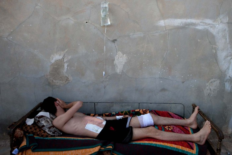 A Syrian man lies on a bed as he recovers from wounds in his stomach and leg made by the deflagration of a shell tank in Kfar Sajna in the northwestern province of Idlib on July 8, 2012. International envoy Kofi Annan has arrived in Syria after admitting that his peace plan has so far failed to end nearly 16 months of blood-shed. (Lolo/AFP/Getty Images)