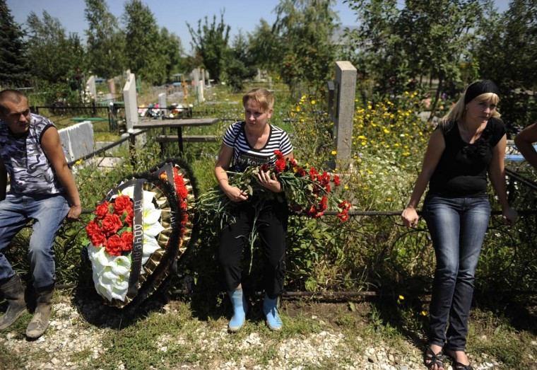 Relatives of one of the victims of the flood mourn during the funerals at a cemetery of the town of Krymsk in the southern Russian Krasnodar region, on July 9, 2012. Russia held a day of mourning for at least 171 people who died in its worst flooding disaster as questions mounted over whether officials did enough to warn of the impending calamity. (Mikhail Mordasov/AFP/Getty Images)