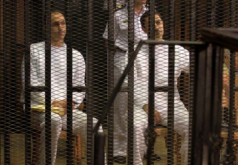Gamal (L) and Alaa Mubarak, sons of ousted president Hosni Mubarak, sit behind bars during their trial in the police academy in the outskirts of Cairo on July 9, 2012. Alaa and Gamal Mubarak appeared in court to face a new corruption trial, after the two were acquitted in another case. (Stringer/AFP/Getty Images)