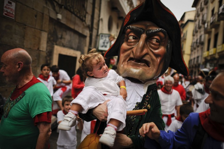 A man dressed as a giant holds a young girl during the giants and big heads parade of the San Fermin festival in the Northern Spanish city of Pamplona. The festival is a symbol of Spanish culture that attracts thousands of tourists to watch the bull runs despite heavy condemnation from animal rights groups. (Pedro Armestre/AFP/Getty Images)