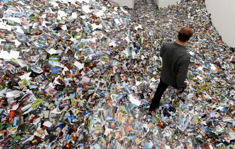 A visitor walks through an installation made of around a million photos downloaded and printed from the image hosting website flickr by Dutch artist Erik Kessels at the Kieler Kunsthalle museum in Kiel, northern Germany. (Carsten Rehder/Getty Images)