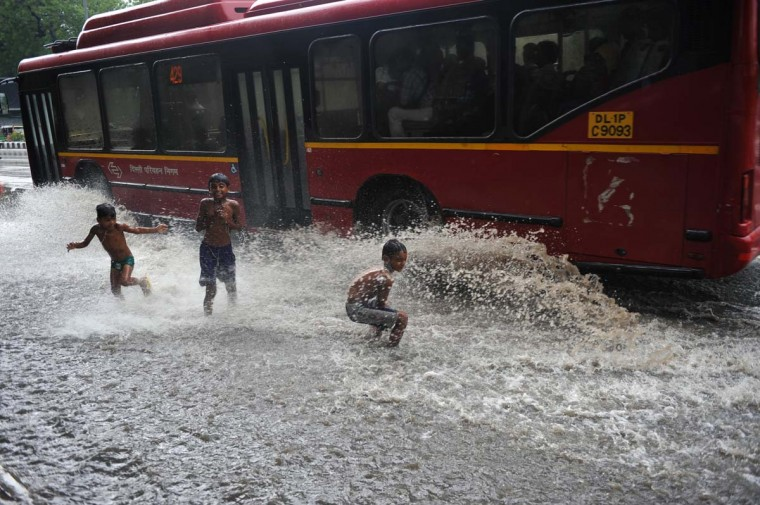 Indian children play in a water-logged street after a spell of monsoon rain in New Delhi. The monsoon rains, a key to India's economy, covered the entire country, but it was 23 percent below average, officials said amid worries of its impact on two cereal-producing states. (Sajjad Hussain/Getty Image)