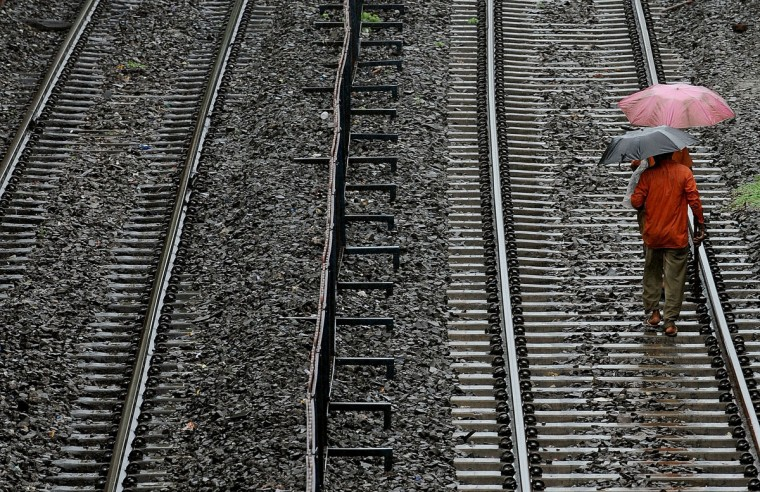 "Indian railway track inspection staff walk along a suburban railway line during a sudden downpour in Mumbai, India.The June to September monsoon is described as the ""economic lifeline"" of India, which has a population of 1.2 billion and is one of the world's leading producers of rice, sugar, wheat and cotton. (Indranil Mukherjee/AFP/Getty Images)"