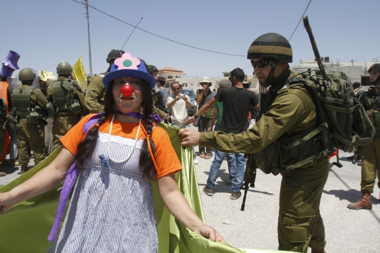 An Israeli soldier pulls the cape of a demonstrator dressed as a clown during a protest against Israel's controversial separation barrier in the West Bank village of Maasarah near Bethlehem. (Musa Al-Shaer/AFP/Getty Images)