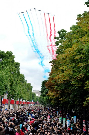 People look at nine alphajets from the French Air Force Patrouille de France releasing trails of red, white and blue smoke, colors of French national flag, as they attend the annual Bastille Day military parade on the Champs-Elysees avenue in Paris July 14, 2012. (Mehdi Fedouach/AFP/Getty Images)
