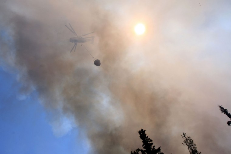 An helicopter flies over a forest fire at the Thessaloniki Seih Sou park, which overlooks the city of Thessaloniki. The risk of new fires was considered high, after several days of hot temperatures accross most of Greece. (Sakis Mitrolidis/AFP/Getty Images)