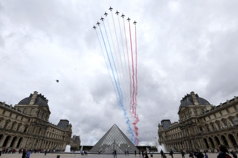Nine alphajets from the French Air Force Patrouille de France release trails of blue, white and red smoke, colors of French national flag, as they fly over Louvre museum and the Louvre Pyramid during the Bastille Day military parade in Paris, on July 14, 2012. (Kenzo Tribouillard/AFP/Getty Images)
