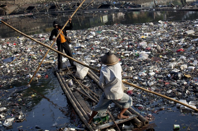 Sanitation workers use a raft to collect litter from a river in Jakarta. Many rivers in Indonesia, especially in many urban areas, are polluted by household and industrial wastes. (Oscar Siagian/AFP/Getty Images)