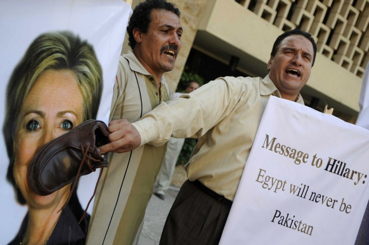"An Egyptian protester shouts slogans as he holds a shoe on a portrait of US Secretary of State Hillary Clinton outside the US embassy in Cairo to protest against her visit to the country. Clinton reaffirmed Washington's ""strong"" support for Egypt's democratic transition, after talks with newly-elected President Mohamed Morsi. (Mohammed Hossam/AFP/Getty Images)"