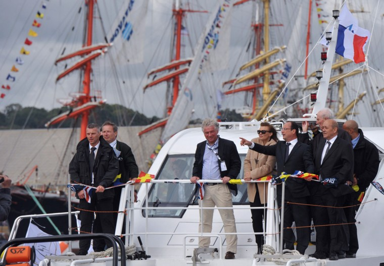 "French President Francois Hollande (2ndR), flanked by his companion Valerie Trierweiler (3rdR), Defence Minister Jean-Yves Le Drian (R) and Brest's Mayor Francois Cuillandre (C), gestures as he stands aboard an electric-power ship, Azenor, to attend the shipping festive event, ""Tonnerres de Brest"" in the Brest bay, western France July 14, 2012. (Alain Jocard/AFP/Getty Images)"