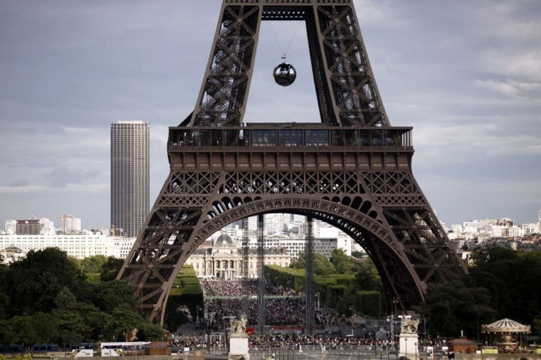 People wait on the esplanade du Champs de Mars for the start of fireworks on the Eiffel Tower, where a giant disco ball has been set, as part of the Bastille Day celebrations on July 14, 2012 in Paris. (Guillaume Baptiste/AFP/Getty Images)
