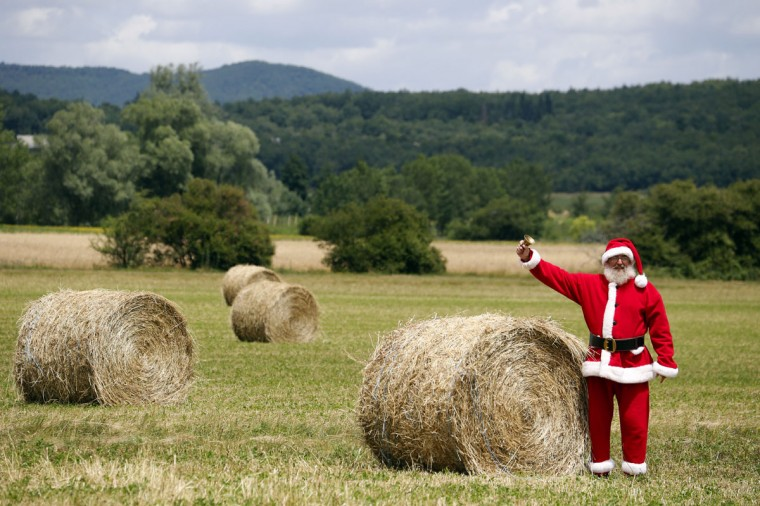 A fan, disguised as a Christmas Father, waits for riders in a field with bales of straw during the the 191 km and fourteenth stage of the 2012 Tour de France cycling race starting in Limoux and finishing in Foix, southern France. (Joel Saget/AFP/Getty Images)