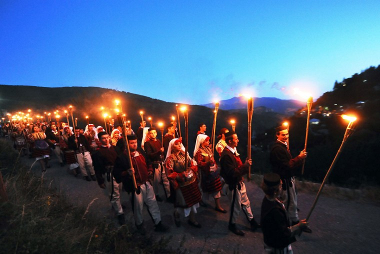 "Young men and women hold torches as they participate in the wedding procession a night before the ceremony ""Galicnik wedding"" in the western Macedonian village Galicnik, some 150 km southwest of Skopje late on July 14, 2012. Every year, around the Christian Orthodox holiday Petrovden (st. Peters day), Macedonians originating from Galicnik gather in this almost deserted mountainous village and a couple gets married according to the old traditions of this region. (Robert Atanasovski/AFP/Getty Images)"