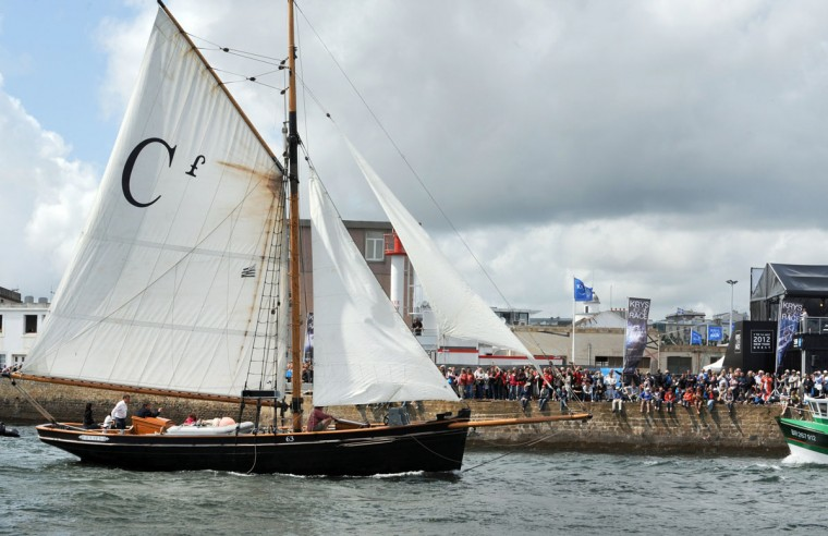 "Hundreds of people gather to welcome the crew in Brest, western France, during the 2012 ""Tonnerres de Brest"" maritime festival on July 15, 2012. (Fred Tanneau/AFP/Getty Images)"